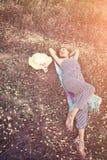Mujer atractiva joven que miente en la hierba que acerca a su sombrero Imágenes de archivo libres de regalías