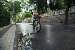 Mujer atractiva joven que monta una bicicleta Imagenes de archivo