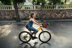 Mujer atractiva joven que monta una bicicleta Imágenes de archivo libres de regalías