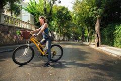 Mujer atractiva joven que monta una bicicleta Foto de archivo libre de regalías