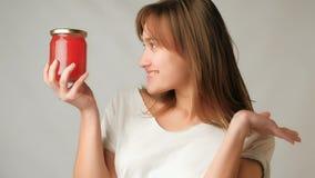 Mujer atractiva joven que muestra asombrosamente el tarro del caviar rojo en el entusiasmo en la cámara almacen de metraje de vídeo