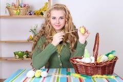 Mujer atractiva joven que pinta los huevos de Pascua Imágenes de archivo libres de regalías