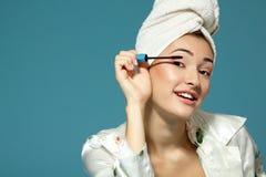 Mujer atractiva joven que pone el rimel del ojo sobre el azul, tre de la belleza Imagen de archivo