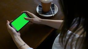 Mujer atractiva joven que practica surf Internet en su teléfono elegante de la pantalla verde en la hora de la almuerzo en pub almacen de metraje de vídeo