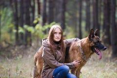Mujer atractiva joven que presenta con el perro de pastor alemán al aire libre en el parque del otoño, cierre para arriba Fotos de archivo