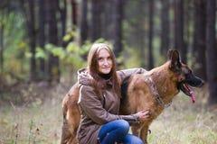 Mujer atractiva joven que presenta con el perro de pastor alemán y que sonríe al aire libre en el parque del otoño, cierre para a Fotografía de archivo