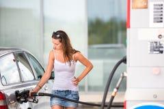 Mujer atractiva, joven que reaprovisiona su coche de combustible en una gasolinera foto de archivo libre de regalías