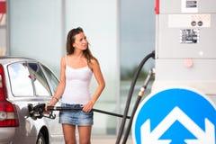 Mujer atractiva, joven que reaprovisiona su coche de combustible en una gasolinera imagen de archivo