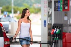 Mujer atractiva, joven que reaprovisiona su coche de combustible en una gasolinera Fotografía de archivo libre de regalías