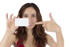 Mujer atractiva joven que señala a una tarjeta de visita en blanco Imagenes de archivo