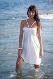Mujer atractiva joven que se coloca en el agua del océano. Imagenes de archivo