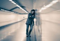 Mujer atractiva joven que se inclina en cansado triste de la sensación de la pared del subterráneo foto de archivo
