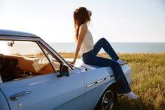 Mujer atractiva joven que se relaja mientras que se sienta en un coche al aire libre Foto de archivo