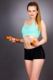 Mujer atractiva joven que se resuelve con pesas de gimnasia fotos de archivo