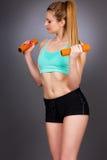 Mujer atractiva joven que se resuelve con pesas de gimnasia imagen de archivo libre de regalías