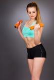 Mujer atractiva joven que se resuelve con pesas de gimnasia fotografía de archivo libre de regalías