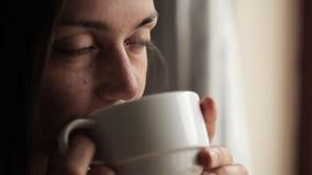 Mujer atractiva joven que se sienta cerca de la ventana y del té de consumición
