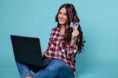 d6c586ea2f65 Mujer atractiva joven que se sienta en la harina con el ordenador y la  tarjeta de