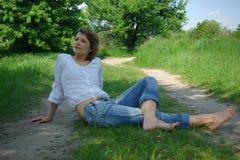 Mujer atractiva joven que se sienta en un camino Foto de archivo libre de regalías