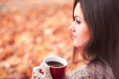 Mujer atractiva joven que se sienta en un parque y un té de consumición imagenes de archivo