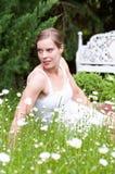 Mujer atractiva joven que se sienta en un prado Foto de archivo libre de regalías