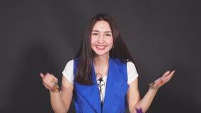 Mujer atractiva joven que sopla confeti de oro de las manos Cámara lenta metrajes