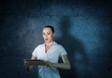Mujer atractiva joven que sostiene una tableta Fotografía de archivo libre de regalías