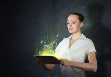 Mujer atractiva joven que sostiene una tableta Imágenes de archivo libres de regalías