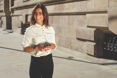 Mujer atractiva joven que tiene conversación de charla sobre el teléfono elegante, el usar feliz de las mujeres celular con el es Imágenes de archivo libres de regalías