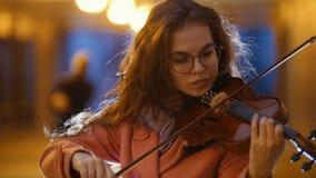 Mujer atractiva joven que toca el violín en subterráneo almacen de metraje de vídeo