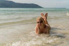 Mujer atractiva joven que toma el sol en el mar Imagen de archivo