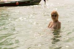 Mujer atractiva joven que toma el sol en una playa Imagenes de archivo