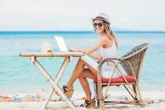 Mujer atractiva joven que usa el ordenador portátil en la playa Trabaja independientemente el trabajo Foto de archivo