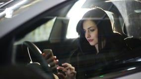 Mujer atractiva joven que usa el teléfono móvil en el coche en el estacionamiento subterráneo Cámara lenta almacen de metraje de vídeo