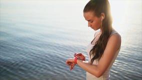 Mujer atractiva joven que usa su reloj elegante almacen de metraje de vídeo