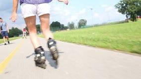 Mujer atractiva joven rollerblading en el parque en un día soleado hermoso, vista de piernas metrajes