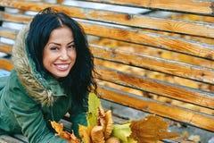 Mujer atractiva joven sonriente con las hojas de arce del otoño en parque en la caída al aire libre Fotos de archivo