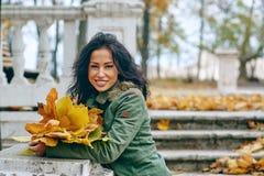 Mujer atractiva joven sonriente con las hojas de arce del otoño en parque en la caída al aire libre Fotos de archivo libres de regalías