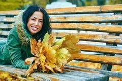 Mujer atractiva joven sonriente con las hojas de arce del otoño en parque en la caída al aire libre Fotografía de archivo libre de regalías