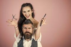 Mujer atractiva La mujer con la maquinilla de afeitar, tijeras cortó el pelo del hombre Imagen de archivo