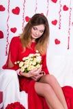 Mujer atractiva magnífica en el vestido rojo que se sienta en el sofá con las flores adentro Fotos de archivo libres de regalías