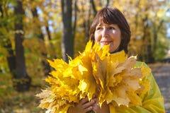 Mujer atractiva mayor que oculta su cara detrás del au del amarillo del brazado Imagen de archivo