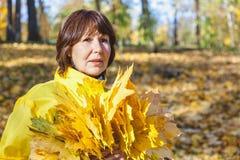 Mujer atractiva mayor que oculta su cara detrás del au del amarillo del brazado Fotos de archivo libres de regalías
