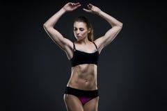 Mujer atractiva muscular de la aptitud en fondo gris en estudio Foto de archivo