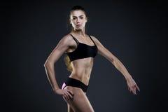 Mujer atractiva muscular de la aptitud en fondo gris en estudio Fotografía de archivo