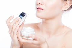 Mujer atractiva que abre una crema de cara Fotos de archivo libres de regalías