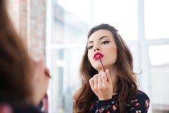 Mujer atractiva que aplica el lápiz labial rojo a los labios que miran en espejo Fotos de archivo
