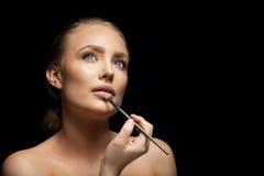Mujer atractiva que aplica lustre del labio Foto de archivo libre de regalías