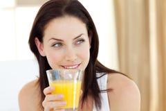 Mujer atractiva que bebe el zumo de naranja Fotos de archivo libres de regalías