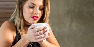 Mujer atractiva que bebe una bebida caliente imagen de archivo